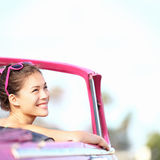 Car woman. Smiling happy enjoying car road trip travel vacation. Young retro woman in pink vintage convertible car looking to side at copy space. Beautiful Royalty Free Stock Photos