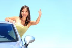 Car woman driver happy. Car. Woman driver happy smiling showing thumbs up coming out of car window on blue summer sky above the clouds. Beautiful young mixed Royalty Free Stock Image