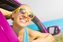 Car woman driver happy. Beautiful girl in a pink car smiling on a background of blue sea Royalty Free Stock Photos