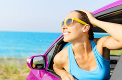Car woman driver happy. Beautiful girl in a pink car smiling on a background of blue sea Royalty Free Stock Photo