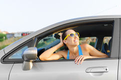 Car woman driver happy. Beautiful girl in a car smiling in yellow sunglasses Royalty Free Stock Image