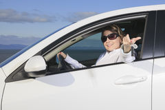 Car. Woman driver happy smiling. A woman driver happy holding a key Royalty Free Stock Photography
