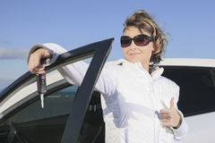 Car. Woman driver happy smiling. A woman driver happy holding a key Royalty Free Stock Images