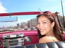 Car woman happy. Car woman smiling happy on passenger seat in pink vintage convertible car. Young mixed race Asian / Caucasian female model during cuba vacation Stock Photography