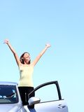 Car woman happy freedom. Concept. Cheering young woman with arms raised stepping out of new car under blue sky. Beautiful young multiracial Asian / Caucasian Royalty Free Stock Photo