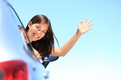 Car woman happy on road trip travel. Car woman happy waving smiling at camera popping head out the window. New car, road trip vacation or drivers license concept Stock Photo