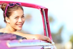 Car woman happy in vintage car. Car woman happy in old pink retro vintage car. Young woman driving on road trip on beautiful sunny summer day. Pretty mixed race Stock Image