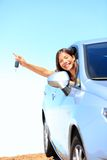 Car woman showing keys. Excited, happy and joyful. Young woman driver smiling in her new car. Mixed race Asian / Caucasian female model above the clouds on stock image
