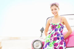 Car woman smiling happy. Standing in front of pink retro vintage car. Portrait of pretty girl in summer dress.  Multicultural Chinese Asian / Caucasian female Royalty Free Stock Photo