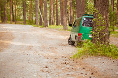 The car in the woods. Green car on a forest road Royalty Free Stock Images