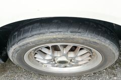 Car with worn bald tire unsafe and poses accident risk Royalty Free Stock Photography