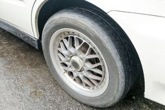 Car with worn bald tire unsafe and poses accident risk Stock Images