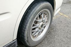 Car with worn bald tire unsafe and poses accident risk Royalty Free Stock Image