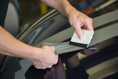 Car wrapper straightening foil with a squeegee. Car wrapper straightening wrapping foil with a squeegee to remove air bubbles Royalty Free Stock Photos