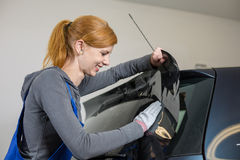 Car wrappers tinting a vehicle window with a tinted foil or film. Using heat gun and squeegee Stock Photo
