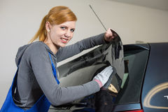 Car wrappers tinting a vehicle window with a tinted foil or film Royalty Free Stock Photos
