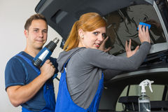 Car wrappers tinting a vehicle window with a tinted foil or film. Using heat gun and squeegee Royalty Free Stock Image