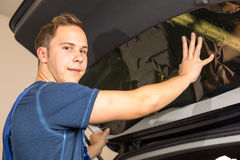Car wrappers tinting a vehicle window with a tinted foil or film. Using heat gun and squeegee Royalty Free Stock Photos