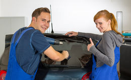 Car wrappers tinting a vehicle window with a tinted foil or film. Using heat gun and squeegee Royalty Free Stock Photography