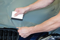 Car wrappers using squeegee to straighten vinyl film Stock Photo