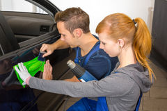 Car wrapping professional wrapping car door handle in colorful foil or film. Using a squeegee stock image
