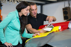 Car wrapping specialist consulting client about vinyl films. Car wrapping professional consulting a client about vinyl films or foils stock image
