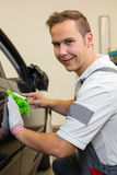 Car wrapping specialist cutting adhesive foil or film with a box cutter. To wrap a car door handle stock photo