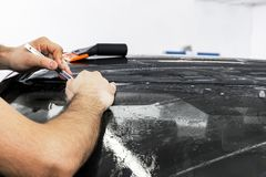 Car wrapping specialist cutting vinyl foil or film on car. Protective film. Applying a protective film with tools for work. Car de. Tailing. Transparent film stock photography