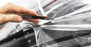 Car wrapping specialist cutting vinyl foil or film on car. Protective film. Applying a protective film with tools for work. Car de. Tailing. Transparent film stock images