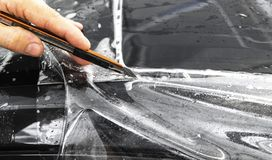 Car wrapping specialist cutting vinyl foil or film on car. Protective film. Applying a protective film with tools for work. Car de. Tailing. Transparent film royalty free stock photos