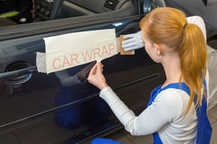 Car wrapping specialist puts logo on vehicle door. Car wrapping professional puts letters made of vinyl foil or film on vehicle door stock image