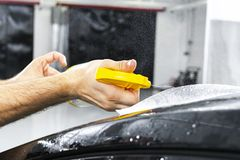 Car wrapping specialist putting vinyl foil or film on car. Protective film. Applying a protective film with tools for work. Car de. Tailing. Transparent film royalty free stock photography