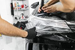 Car wrapping specialist putting vinyl foil or film on car. Protective film. Applying a protective film with tools for work. Car de. Tailing. Transparent film stock photo