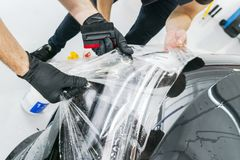 Car wrapping specialist putting vinyl foil or film on car. Protective film. Applying a protective film with tools for work. Car de. Tailing. Transparent film stock images