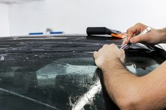 Car wrapping specialist putting vinyl foil or film on car. Protective film. Applying a protective film with tools for work. Car de. Tailing. Transparent film royalty free stock images