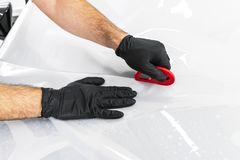 Car wrapping specialist putting vinyl foil or film on car. Protective film on the car. Applying a protective film to the car with. Tools. Car detailing stock photography