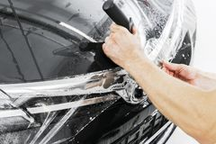 Car wrapping specialist putting vinyl foil or film on car. Protective film on the car. Applying a protective film to the car with. Tools. Car detailing stock photos