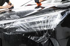 Car wrapping specialist putting vinyl foil or film on car. Protective film on the car. Applying a protective film to the car with. Tools. Car detailing royalty free stock photo
