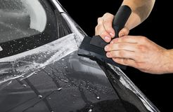 Car wrapping specialist putting vinyl foil or film on car. Protective film on the car. Applying a protective film to the car with. Tools for work. Car detailing royalty free stock photo