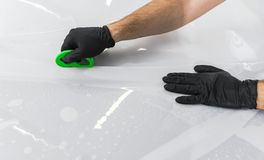 Car wrapping specialist putting vinyl foil or film on car. Protective film on the car. Applying a protective film to the car with. Tools for work. Car detailing stock photography