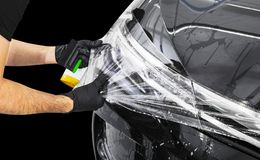 Car wrapping specialist putting vinyl foil or film on car. Protective film on the car. Applying a protective film to the vehicle w. Ith tools for work. Car stock images