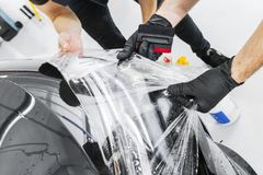 Car wrapping specialist putting vinyl foil or film on car. Protective film on the car. Applying a protective film to the car with. Tools. Car detailing royalty free stock image