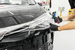 Car wrapping specialist putting vinyl foil or film on car. Protective film on the car. Applying a protective film to the car with. Tools. Car detailing royalty free stock images