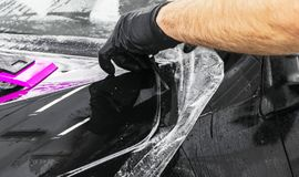 Car wrapping specialist putting vinyl foil or film on car. Protective film on the car. Applying a protective film to the car with. Tools. Car detailing stock image