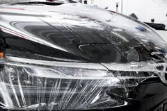 Car wrapping specialist putting vinyl foil or film on car. Protective film on the car. Applying a protective film with tools for w. Ork. Car detailing royalty free stock photos