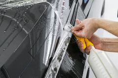 Car wrapping specialist putting vinyl foil or film on car. Protective film. Applying a protective film with tools for work. Car de. Tailing. Transparent film stock image