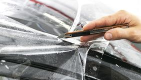Car wrapping specialist putting vinyl foil or film on car. Protective film. Applying a protective film with tools for work. Car de. Tailing. Transparent film stock photography