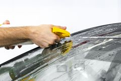 Car wrapping specialist putting vinyl foil or film on car. Protective film. Applying a protective film with tools for work. Car de. Tailing. Transparent film royalty free stock image