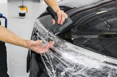 Free Car Wrapping Specialist Putting Vinyl Foil Or Film On Car. Protective Film On The Car. Applying A Protective Film To The Car With Royalty Free Stock Photo - 135036555