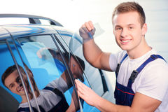 Car wrapping specialist in the station. Welcome to our car service station. Closeup image of a handsome car mechanic attaching tinting foil to car window and Stock Photos